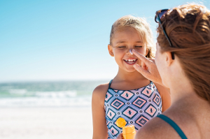 Mother applying sunscreen to her daughter at the beach