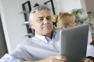 Senior citizen reading news on a tablet