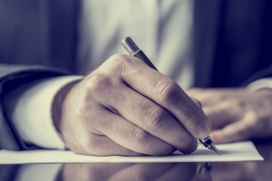 Close up of a man's hands signing a document