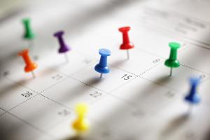 Closeup of calendar with thumb tacks on various dates