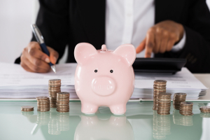 Closeup of business woman calculating her savings with a piggy bank and stacks of coins