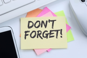 Post-it with the words Don't Forget on a desk near a keyboard mouse