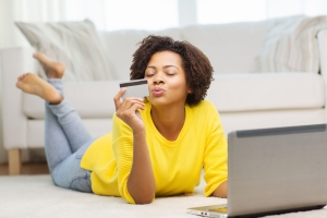 Woman at home with laptop and debit card