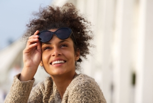 Close up portrait of a happy smiling young woman outside with sunglasses