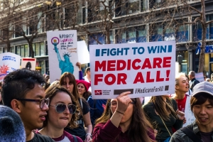 """Participant to the Women's March event holds """"Medicare for all"""" sign while marching on Market street in downtown San Francisco"""
