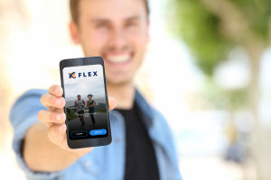 Man holding a mobile phone displaying the Flex mobile app