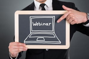 Man holding a chalkboard with the word webinar